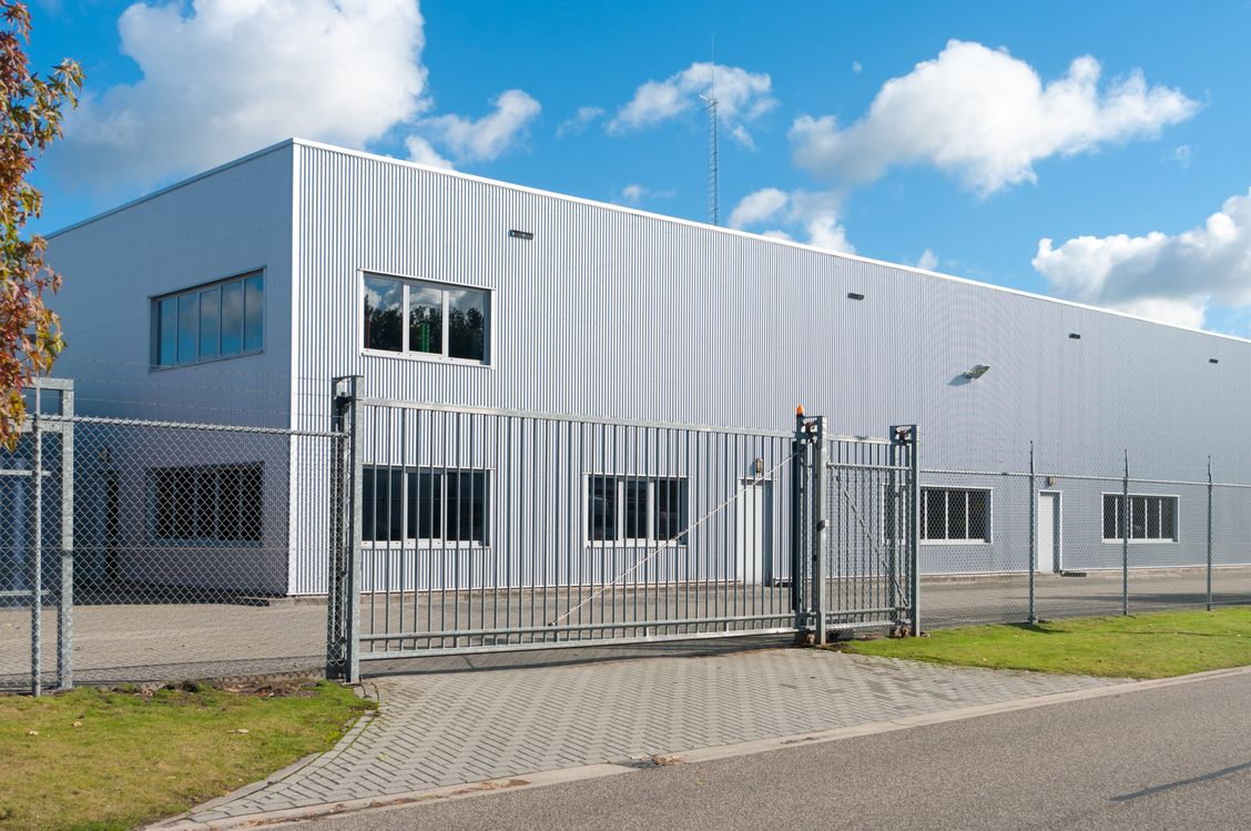 industrial building with a chain link perimeter fence and automatic access gate