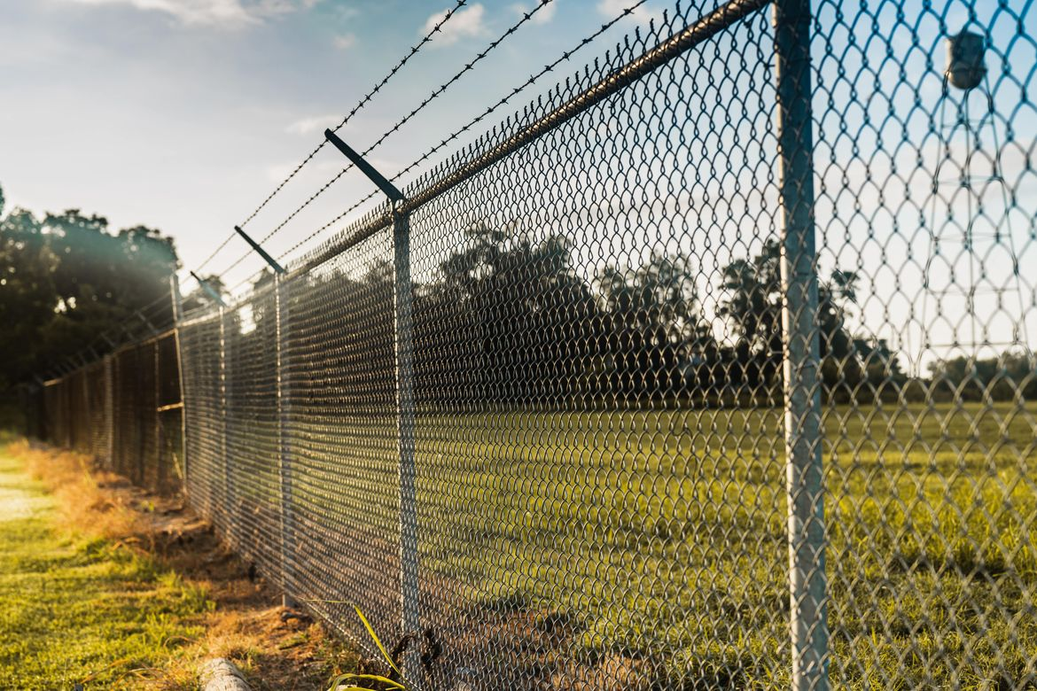 barbed wire chain link fencing surrounding the perimeter of a large commercial landscape